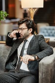 호텔 로비의 안락의자에 앉아 스마트폰으로 말하는 성공적인 중동 사업가의 세로 허리