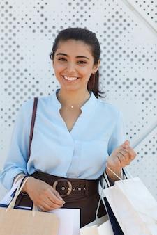 쇼핑백을 들고 야외에서 질감 된 흰색 표면에 서있는 동안 카메라에 웃 고 젊은 여자의 초상화를 세로 허리
