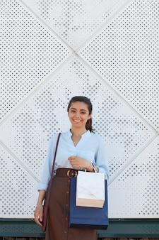 쇼핑 가방을 들고 쇼핑몰에서 야외에 서있는 동안 카메라에 웃고 젊은 여자의 초상화를 수직 허리, 위의 공간을 복사