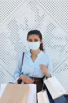 쇼핑 가방을 들고 마스크를 착용하는 젊은 여성의 세로 허리 위로 표면, 유행성 쇼핑 후 질감에 대해 서있는 동안