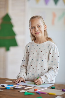 Vertical waist up portrait of smiling blonde girl looking at camera while standing by crafting table and enjoying art class in school