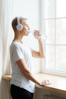 Vertical waistup portrait of happy senior woman drinking water from plastic bottle after fitness at home