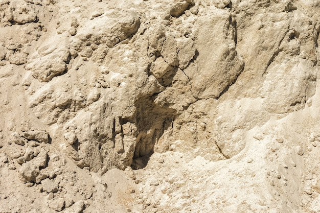 Vertical wall of a sand pit as a natural background yellow sand