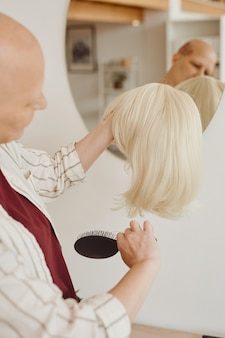 Vertical warm-toned portrait of bald woman brushing wig while standing by mirror in minimal home interior, alopecia and cancer awareness