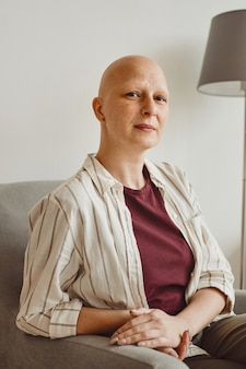 Vertical warm-toned portrait of confident bald woman looking at camera while sitting on couch in minimal home interior, alopecia and cancer awareness