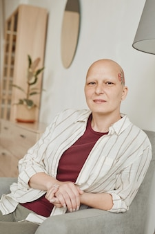 Vertical warm-toned portrait of confident bald woman with head tattoo looking at camera while sitting on couch in home interior, alopecia and cancer awareness