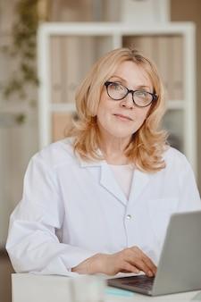현대 병원 사무실에서 책상에서 작업하는 동안 카메라를 찾고 성숙한 여성 의사의 세로 따뜻한 톤의 초상화