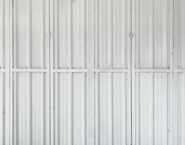 수직 풍화된 강철 셔터 문 벽 배경입니다.