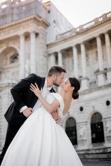 Вертикальное свадебное фото жениха и невесты за мгновение до поцелуя перед историческим зданием