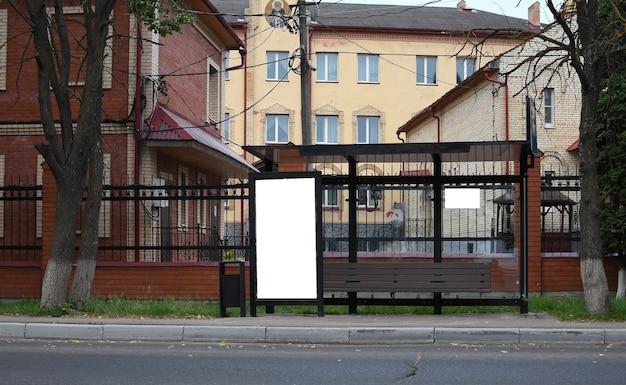 街の通りの夏の日のガラスのバス停で垂直の白い看板