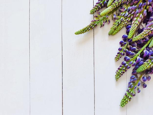 縦型のホワイトボードと紫のルピナス。花に写真を集中させます。上面図、招待状の基礎、製品の背景、花柄のフラットレイ。