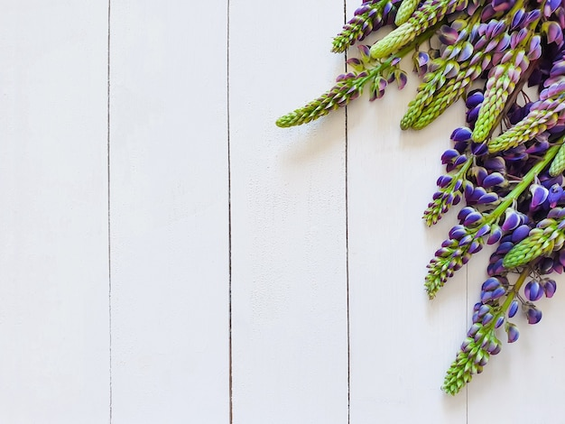 Vertical white boards and purple lupins. focus photos on flowers. top view, basis for invitation, product background, floral flat lay.