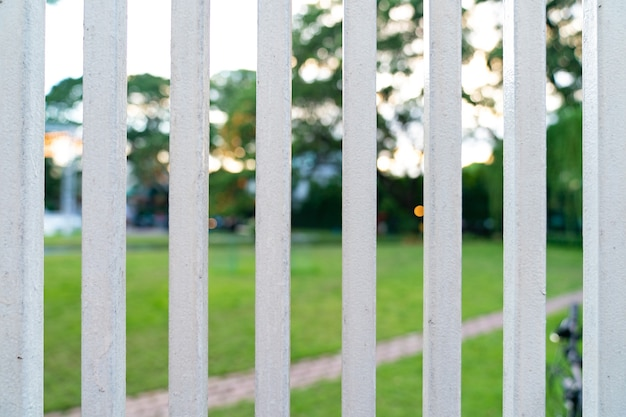 정원의 수직 흰색 강철 울타리 그릴 앞.