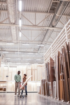Вертикальный широкоугольный портрет афро-американских отца и сына, делающих покупки вместе в строительном магазине, стоящего с тележкой на острове из дерева и досок, копировальное пространство