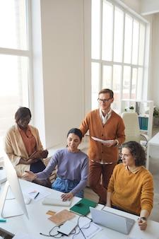 Вертикальный широкоугольный портрет разнородной команды ит-разработчиков, обсуждающей проект во время работы над производством программного обеспечения в офисе, копирование пространства