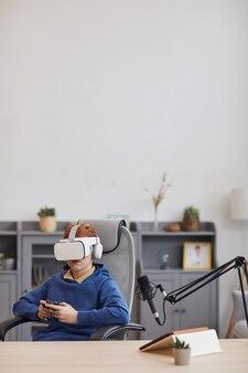 Вертикальный широкоугольный портрет мальчика-подростка в гарнитуре vr и держащего геймпад во время игры в захватывающие видеоигры дома, копия пространства