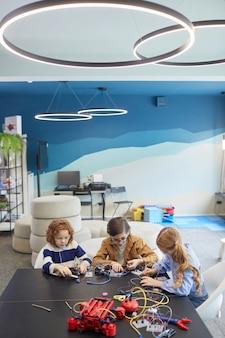 Вертикальный широкоугольный портрет трех симпатичных детей, строящих роботов во время инженерных занятий в школе развития, копировальное пространство