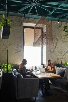 Вертикальный широкоугольный портрет двух современных мужчин, использующих ноутбуки во время работы за столиком в кафе, освещенным солнечным светом, в зеленом интерьере лофта, копия пространства