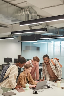 Вертикальный широкоугольный снимок разнообразной группы молодых студентов, использующих ноутбук вместе во время работы над школьным проектом в колледже, копия пространства