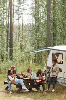 キャンプしながら屋外でピクニックを楽しんでいる若者の多様なグループの垂直広角ビュー...