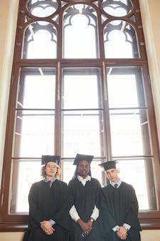 고전 학교의 화려한 창문 옆에 서서 졸업 가운을 입은 세 젊은이의 수직 광각 보기, 복사 공간
