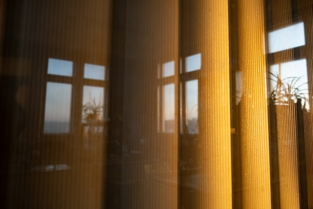 Вертикальные широкие жалюзи за окном в лучах заката, отражение офисных окон.