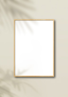 Vertical wooden picture frame hanging on a light beige wall.
