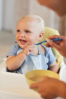 Вертикальный снимок неузнаваемой женщины, кормящей кашей своего веселого маленького сына
