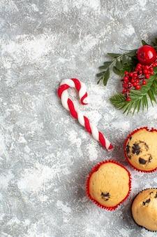 Vista verticale di piccoli cupcakes, caramelle e rami di abete, accessori per la decorazione del cono di conifere sul lato destro sulla superficie del ghiaccio
