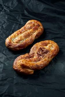 Vertutaのビューを閉じます-黒いテーブルの上のリンゴと排気生地からロールします。モルダビア料理とウクライナ料理の美味しくて繊細なペストリー。上面図。セレクティブフォーカス