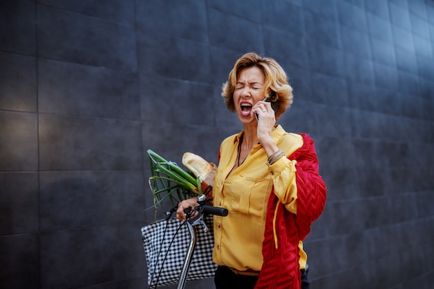 Very angry attractive blonde caucasian senior woman shouting and arguing over the smart phone