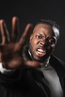 Очень сердитый темнокожий мужчина говорит вам остановиться с распростертыми руками, борясь за свои права. закройте вверх. черный фон.