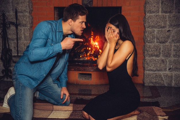 Very angry and rude man stand on knees and point on young woman. his look is full of maddness. young woman cover face with hands. she is scared and need help. they sit at fireplace.