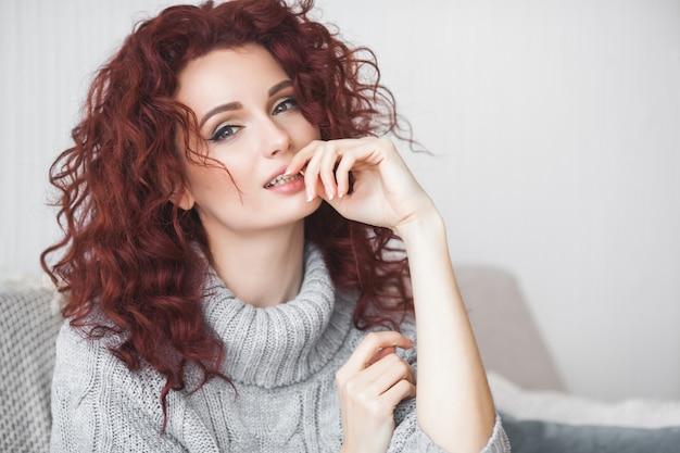 Очень привлекательная молодая женщина в помещении. портрет вьющиеся волосы женщины. рыжая красивая женщина у себя дома.