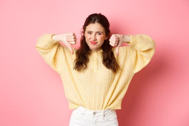 Очень плохо. разочарованная молодая женщина жалуется на что-то ужасное, показывает неприязнь с большими пальцами вниз, гримасничает и хмурится, качает головой, дает отрицательный отзыв, розовая стена