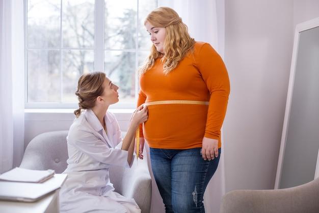 非常に悪い結果。太った女性と話し、彼女を測定する決心したプロの栄養士