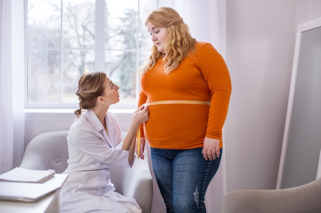 Very bad results. determined professional nutritionist talking with a fat woman and measuring her