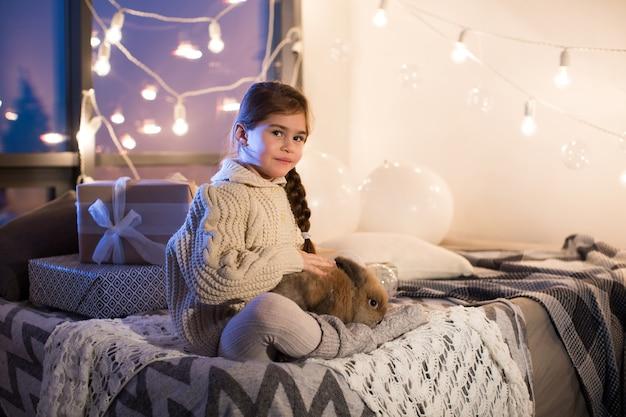 Очень красивая и очаровательная маленькая темноволосая женщина в белом свитере держит живого кролика