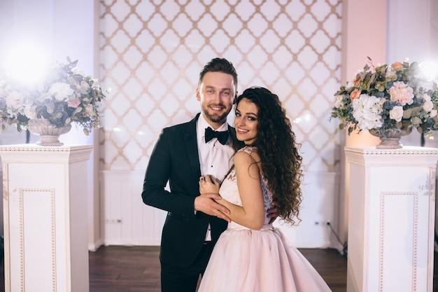 매우 아름답고 행복한 신혼 부부가 결혼식에서 아름답게 장식 된 웨딩 아치 근처에 서 있습니다.