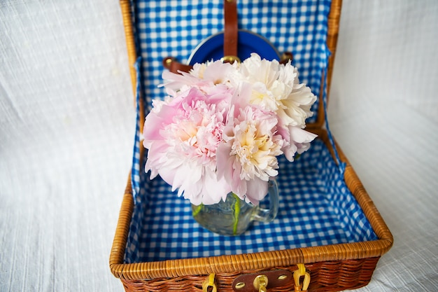 A very beautiful bouquet of pink peonies stands in a vase on a wooden suitcase.