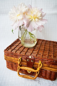Very beautiful bouquet of pink peonies in a vase stands on a wooden suitcase.