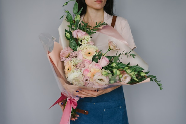 Very beautiful florist woman holding a beautiful colorful blooming bouquet of flowers on a gray wall background.