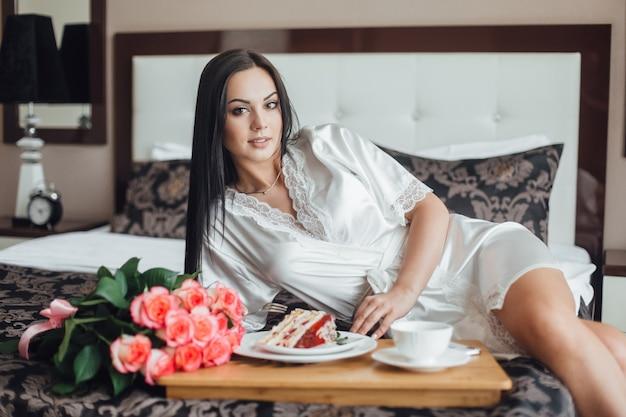 Molto bella ragazza bruna sdraiata sul letto la mattina nella sua stanza, vicino a un vassoio con un pezzo di torta con caffè e un mazzo di rose.