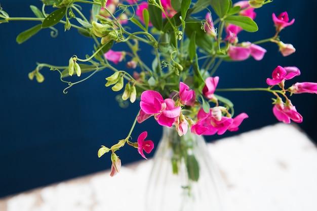古いテーブル、クローズアップの花瓶に非常に美しい小さなピンクの花