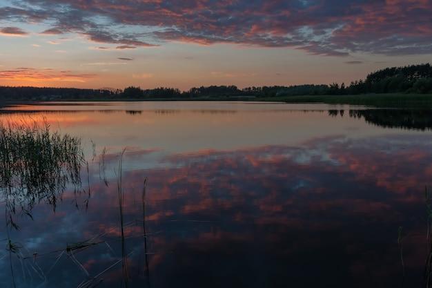 Очень красивый величественный закат, отражение ярких облаков в тихой воде