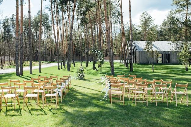 花と森の金属のアーチで非常に美しい外式古典的な結婚式