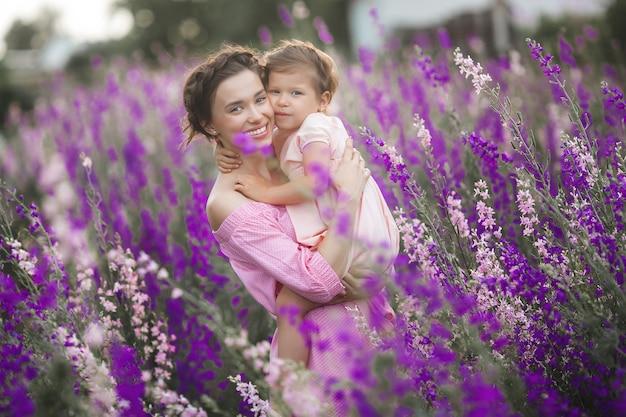 花畑の若い母と子の非常に美しい写真
