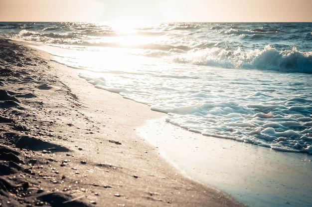 해변의 젖은 모래에 있는 태양의 매우 아름다운 반사, 톤 및 필터