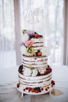 Very beautiful rustic wedding cake decorated with flowers