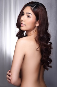 Very beautiful transgender model woman topless to present skin and curl hair over white curtain fashion style, studio lighting professional make up